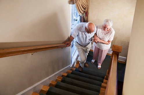 Wife helping husband up the stairs
